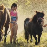 Louise Sedgman has captured a moment of family fun as her daughters Grace and Emma play under the sprinklers with their 'worth-their-weight-in-gold' ponies Petal and Midnight on a hot summer's evening.