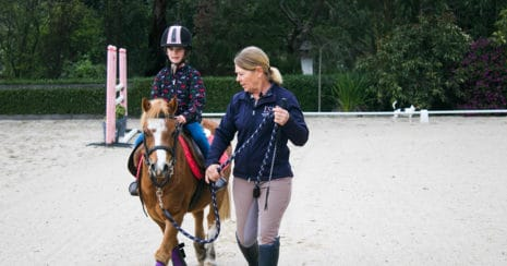 Adult instructor with child on pony in arena. From Little Trainers, Big Trainers Grow. Teaching kids to train their ponies.