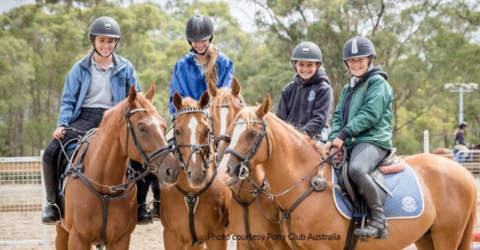 Four members of the Tasmanian Pony Club, Huntingfield, smile for the camera on their chesnut horses. Future proofing Pony Club