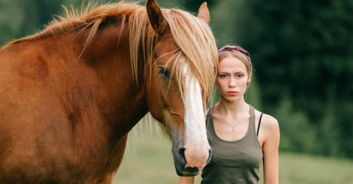 a young woman looking serious stands next to a chesnut horse