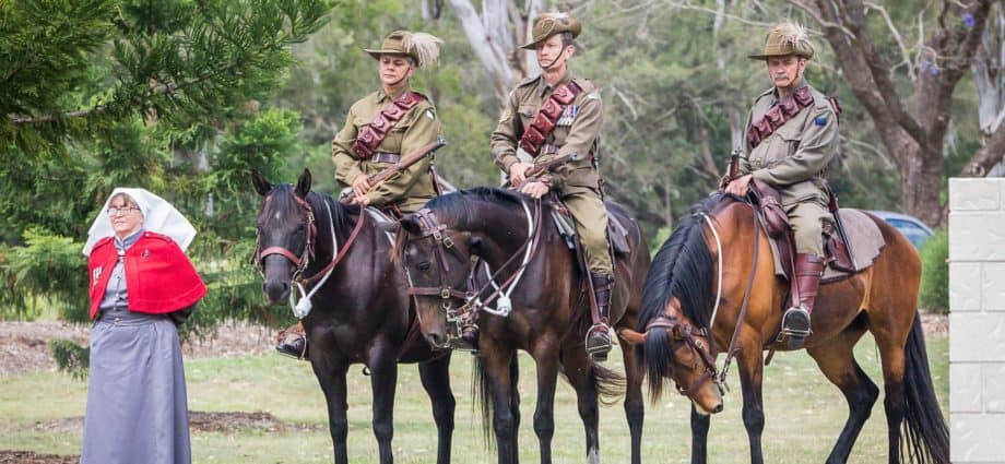 Three men in World War One AIF Lighthorse uniforms, slouch hat with feather mounted on horseback. Horses are tacked with replica Lighthorse military tack. Beside them stand a woman in Nurse outfit. Commemorating Rememberance Day. ANZAC Day. Lest We Forget